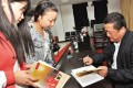 Li Yuanchuan signs copies of one of his novels, focused on the problems of smog, for two new readers. Photo: SCMP Pictures