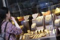 A woman looks at gold products in a jewellery shop in Tsim Sha Tsui. Photo: David Wong