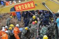 Rescuers carry the body of a victim after being pulled out among the debris at the landslide site in Shenzhen, south China's Guangdong province on December 23. Photo: Reuters