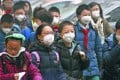 Pupils wearing masks walk on a smog-shrouded street for a school event in Beijing on Christmas Day. Photo: Xinhua
