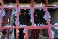 Afghans peer through the broken windows of a bakery at the site of a suicide car bomb blast near the international airport in Kabul on Monday that killed one person. Photo: AFP