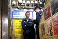 Police officers check the locked front door of Causeway Bay Books in Lockhart Road, Causeway Bay. Photo: Felix Wong