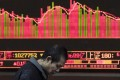 An investor walks in front of a screen showing stock market movements at a securities company in Beijing. Photo: AFP