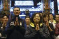 Taiwan's Democratic Progressive Party presidential candidate Tsai Ing-wen (centre) prays at a temple during a campaign stop in Beigang, Taiwan. Photo: Reuters