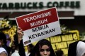 Women hold placards during a vigil outside the damaged Starbucks coffee shop in central Jakarta on January 15, 2016, a day after a series of explosions hit the Indonesian capital. Photo: AFP