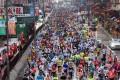 Hundreds of runners pass along Nathan Road in Mong Kok during yesterday's Hong Kong Marathon. Photo: Dickson Lee