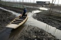 A fisherman tries to paddle his boat through a small stream amid the partially dried-up Honghu Lake in Honghu, Hubei province. Photo: Reuters