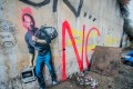 """Artwork by Banksy decorates a wall in """"The Jungle"""" migrant camp in the port of Calais, France. The artwork alludes to the fact that Apple founder Steve Jobs was the son of a Syrian immigrant. Photo: EPA"""
