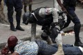 A man lays wounded on the ground after being attacked by demonstrators in Port-au-Prince, Haiti. Photo: EPA