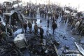 Syrian pro-government forces and residents gather at the site of suicide bombings. Photo: AFP