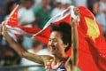 Wang Junxia drapes herself in the Chinese flag after winning the 5,000m race at the 1996 Atlanta Olympics. Photo: Reuters