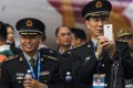 A PLA officer takes photos on his mobile phone at the Zhuhai air show in 2014. The military warned personnel this week in its daily newspaper that car hailing apps could use a phone's GPS system to reveal sensitive information. Photo: Reuters