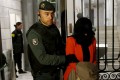 One of the directors of the Industrial and Commercial Bank of China's Madrid office is lead away from the bank's headquarters after being arrested during a raid on Wednesday. Photo: Reuters