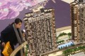 A homebuyer views a model of the Twin Regency project displayed at Yoho Town in Yuen Long. Photo: K.Y. Cheng