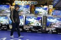 A shopper walks past Sharp Aquos flat-panel televisions at an electronics store in Tokyo. Photo: AP