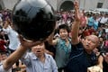 Soccer fans beat a black football which symbolises dark Chinese football industry as they protest outside a stadium in downtown Wuhan city in 2008. Despite a clampdown on corruption since then, problems still remain. Photo: EPA