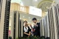 A sales assistant speaks to a customer in front of a model of a residential complex at a real estate exhibition in Shanghai on April 30, 2015. Photo: Reuters