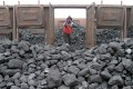 A worker loads a freight train with coal at a station in Shenyang, northeast China's Liaoning province. Photo: EPA