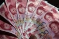 A former primary school student who stole 10 Chinese cents from her classmate more than 40 years ago tried to hand 10,000 yuan to her when they met again on Sunday. Photo: EPA