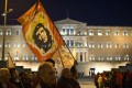 """A protester holds a flag with the image of revolutionary hero Ernesto """"Che"""" Guevara, as members of the Communist-affiliated PAME demonstrate outside the Greek parliament against new bailout measures in March. Photo: AP"""