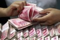 A clerk counts Chinese banknotes at a bank. Photo: AP