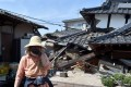 A woman stands in front of her damaged house in Mashiki, Kumamoto prefecture. Photo: AFP