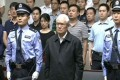 Zhou Yongkang, China's former domestic security chief, stands between his police escorts as he listens to his sentence for corruption and other crimes in a court in Tianjin in June. Photo: Reuters/China Central Television