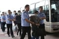 Fugitives allegedly involved in economic crimes are escorted at Beijing Capital International Airport in June 2015. Photo: Xinhua