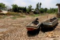 Two boats lie on cracked ground in a dry area in Ca Mau province, Vietnam. Photo: EPA