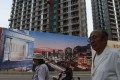 People walk past a billboard advertising a new housing complex outside a construction site in Beijing. Photo: AFP