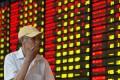 An investor follows stock movements at a trading hall in Nanjing, capital city of east China's Jiangsu province. Photo: Xinhua