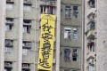 A large yellow banner draped outside a residential building next to an elderly home in Tseung Kwan O visited by Zhang Dejiang on Thursday. Photo: Nora Tam