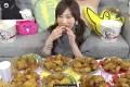 A screen grab from a YouTube video of petite Japanese performer Kinoshita Yuka eating four buckets of KFC chicken live.