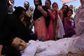 Mourners stand beside the body of transgender activist Alisha at her funeral in in Peshawar, Pakistan, on Thursday. Photo: EPA