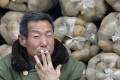 A vendor smokes a cigarette in front of sacks of potatoes piled up on a truck at a market in Shanxi province. Photo: Reuters