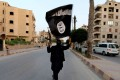 In this June 2014 file photo, a member loyal to Islamic State waves a flag in Raqqa in Syria. Photo: Reuters