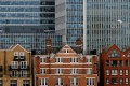 Long office leases seen protecting investors from short-term fluctuations. Photo: Reuters Apartment buildings are backdropped by skyscrapers of banks at Canary Wharf in London, Britain October 30, 2015. REUTERS/Reinhard Krause/File Photo