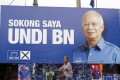 """A Malaysian ethnic Chinese woman rides past a billboard of Prime Minister Najib Razak which translates """"I vote for National Front coalition"""" ahead of the 2013 general election. The next general election is scheduled for 2018. File photo: AP"""
