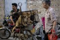 A woman walks past a dog vendor with three animals in a cage, as he waits buyers in Yulin. Photo: AP