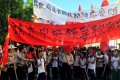"""Villagers carry banners which read """"Plead the central government to help Wukan"""" (in red) and """"Wukan villagers don't believe Lin Zuluan took bribes"""" during a protest in Wukan, Guangdong province on Wednesday. Photo: Reuters"""