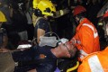 An injured fireman battling the blaze inside the industrial building is rushed into an ambulance yesterday. Photo: SCMP Pictures