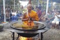 """A monk sits in a vat of """"boiling oil"""" in Thailand's Nong Bua Lamphu province."""