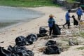Workers cleaning up Nim Shue Wan beach on Lantau Island. Photo: Reuters