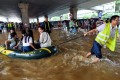 A rescuer helps people with an inflatable boat in flood water in Wuhan, Hubei province. Photo: AFP