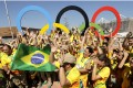 Volunteers cheer around a set of Olympic rings in Rio de Janeiro, Brazil, prior to the start of the 2016 games. Photo: AP