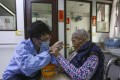 Personal care worker assisting an elderly resident to eat. Photo: Jonathan Wong