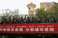 """Paramilitary policemen in Xinjiang behind a banner reading """"Harmony and stability are blessings, separation and discord are disasters"""". Photo: Reuters"""