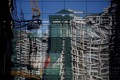 A construction site and a residential building are reflected in the glass wall of a building in Beijing. To fully understand China, one must first understand the rest of the world. Photo: Reuters