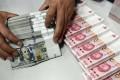 A clerk counts Chinese yuan and US dollar banknotes at a bank in China. Photo: Reuters