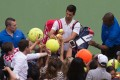 Novak Djokovic signs autographs for fans after his brief appearance against Mikhail Youzhny. Photo: AFP